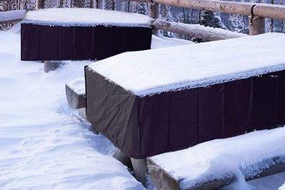 Gartenmöbel mit Schutzhülle im Winter bei Schnee