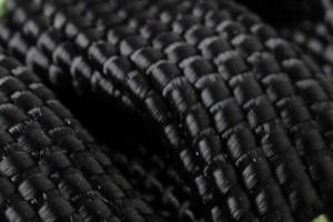 das Bild zeigt in Nahaufnahme das Polyester Gewebe eines flexiblen Gartenschlauchs